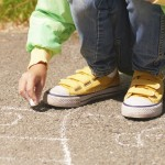 Little girl drawing a hopscotch board on asphalt